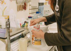 Une employée de Terre à Soi remplit un contenant de dentifrice à la section vrac